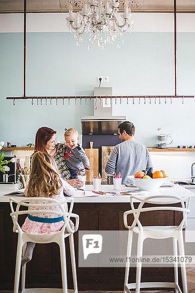 Frau sieht den Sohn an  während sie neben der Tochter steht  die in der Küche lernt