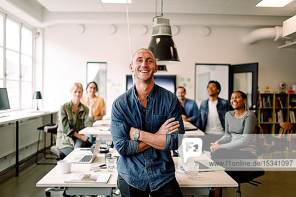 Portrait of smiling male entrepreneur standing with arms crossed and employees sitting at office desk