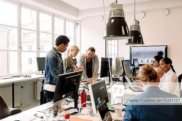 Kreative Geschäftsleute  die im Großraumbüro am Computer arbeiten