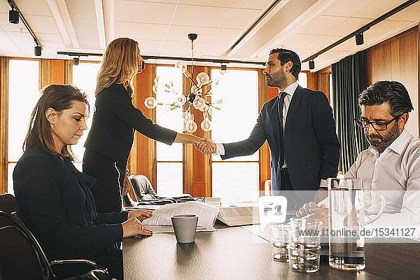 Männliche und weibliche Mitarbeiter bei der Arbeit  während Anwälte in einer Anwaltskanzlei am Tisch Hände schütteln