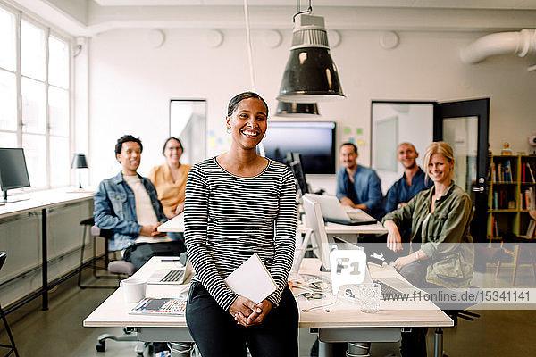Lächelnde Geschäftsfrau sitzt am Schreibtisch  während die Kollegen im Hintergrund