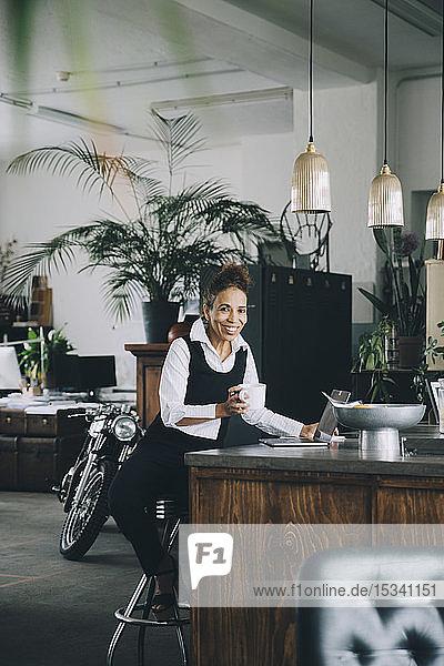 Porträt einer lächelnden Geschäftsfrau  die eine Kaffeetasse hält  während sie auf einer Kücheninsel in einem kreativen Büro sitzt
