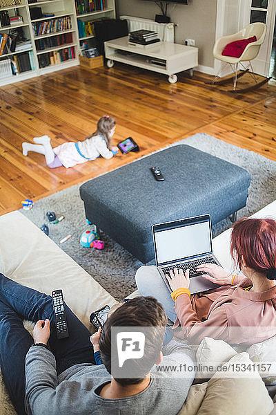 Hochwinkelansicht einer Frau  die am Laptop arbeitet  während sie zu Hause von einem Mann auf dem Sofa sitzt
