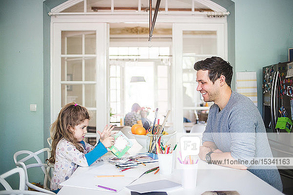 Smiling father looking at girl holding picture book in kitchen