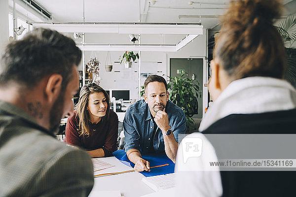 Selbstbewusste Unternehmer und Unternehmerinnen am Tisch während eines Treffens im Kreativbüro