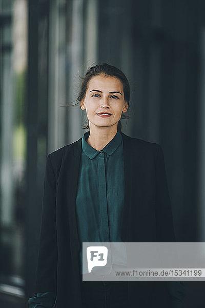 Porträt einer selbstbewussten Geschäftsfrau  die in der Stadt steht