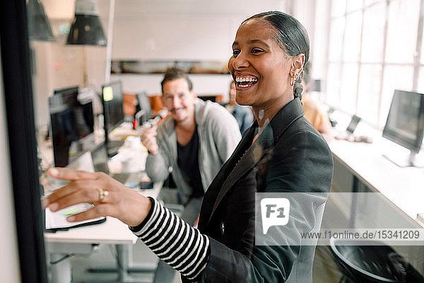 Lächelnde Geschäftsfrau diskutiert mit einem Kollegen  der im Büro durch Glas gesehen wird