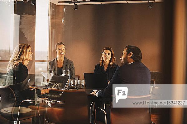 Männliche und weibliche Berater diskutieren am Konferenztisch bei Bürobesprechung