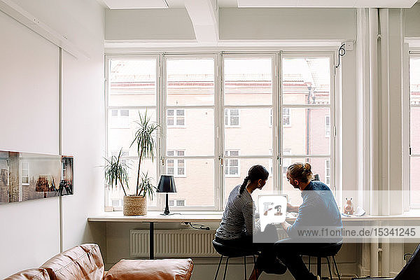 Male and female business colleagues looking at camera while sitting by desk in creative office
