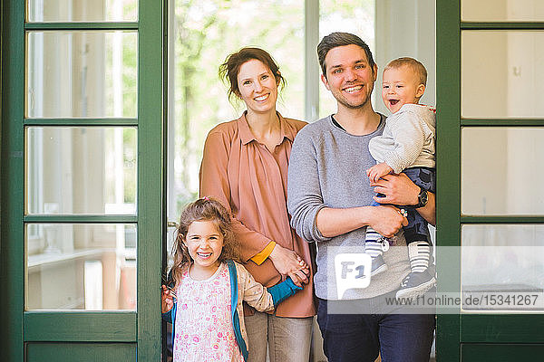 Portrait of happy family standing at home entrance