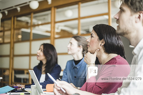 Male and female coworkers listening in meeting at board room