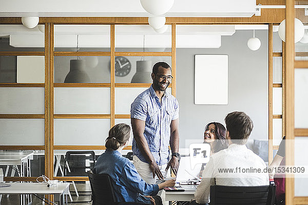 Smiling businessman discussing business plan with colleagues in meeting at board room