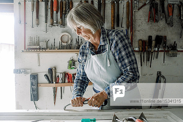 Confident senior female entrepreneur scraping on window frame at store workshop