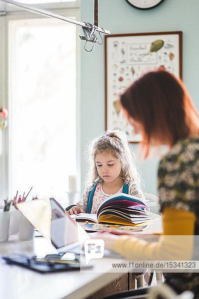 Seitenansicht einer Frau  die einen Laptop benutzt  während sie neben einem Mädchen sitzt  das auf der Kücheninsel lernt