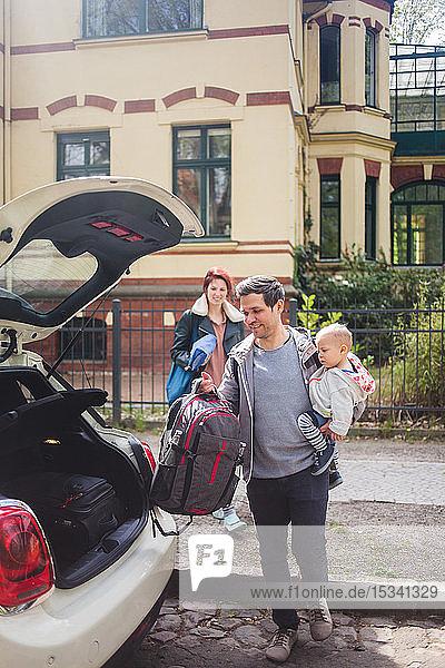 Frau sieht Mann an  der einen Sohn trägt  während sie Gepäck in den Kofferraum eines Autos legt