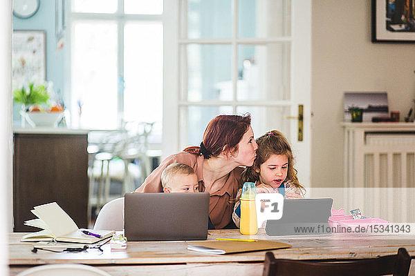 Mittlere erwachsene Frau küsst Tochter  während sie mit Sohn zu Hause sitzt