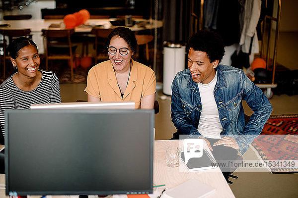 Lächelnder Unternehmer und Unternehmerin sitzen am Arbeitsplatz nebeneinander