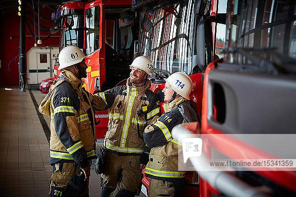 Gruppe von Feuerwehrleuten  die sich unterhalten  während sie in der Feuerwache gegen ein Feuerwehrauto stehen