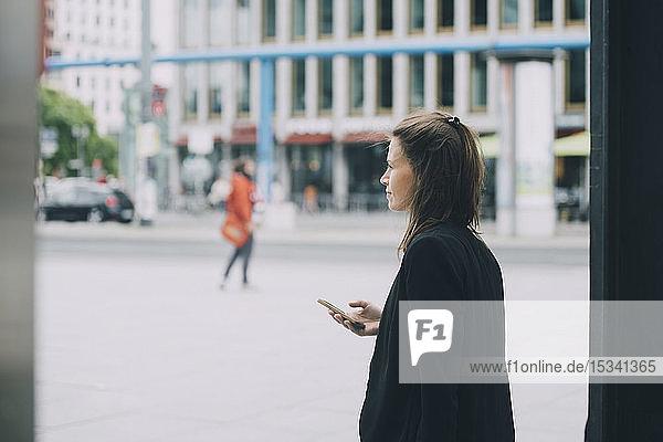 Seitenansicht einer selbstbewussten Geschäftsfrau  die ihr Mobiltelefon beim Gehen auf der Straße in der Stadt in der Hand hält