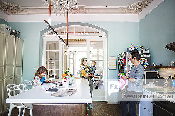 Lächelnde Frau  die einen Sohn trägt  während sie mit einem Mann spricht  der zu Hause in der Küche steht