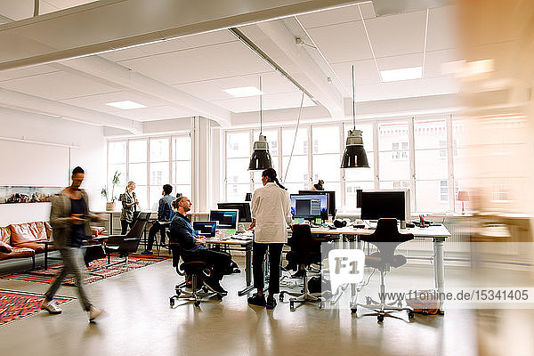 Male and female business colleagues working in creative office space