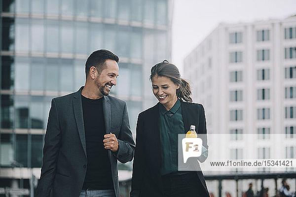 Lächelnde Geschäftsfrau und Geschäftsmann unterhalten sich beim Spaziergang in der Stadt