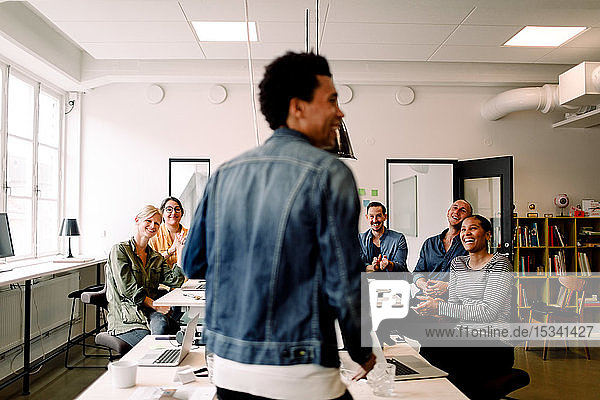 Rear view of smiling colleagues looking at businessman in office