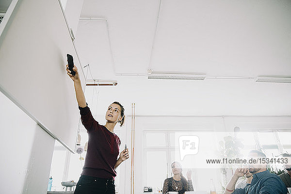 Businesswoman explaining colleagues over whiteboard during meeting in creative office