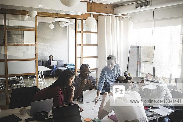 Männliche und weibliche Mitarbeiter diskutieren über Geschäftsmann bei Bürobesprechung durch Glaswand gesehen