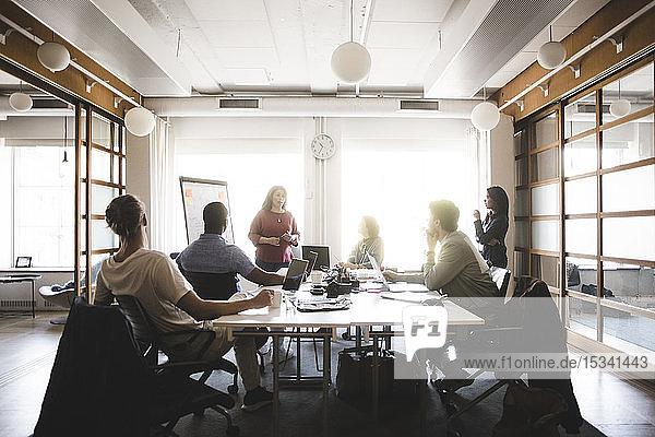 Geschäftsfrau bespricht Geschäftsstrategie mit Kollegen bei Besprechung im Sitzungssaal