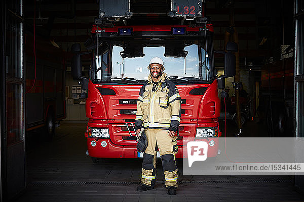 Full length portrait of smiling male firefighter standing in front of fire engine at fire station