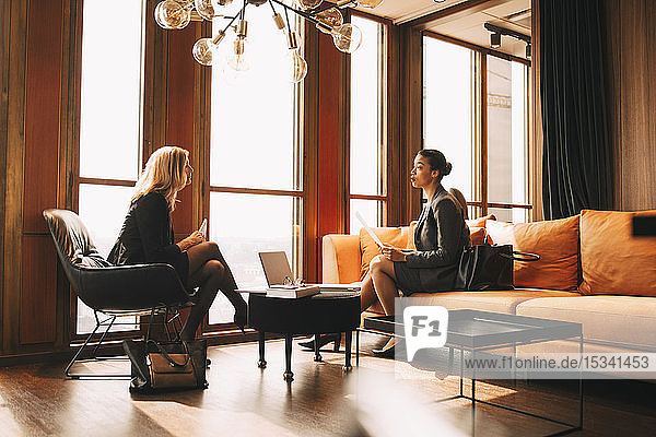 Juristinnen diskutieren in voller Länge  während sie im Büro am Fenster sitzen