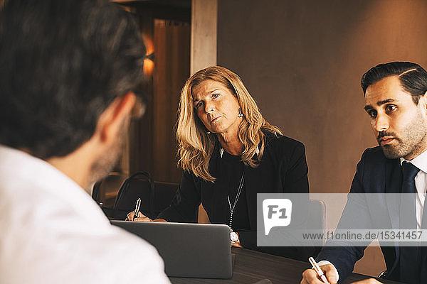 Seriöse juristische Mitarbeiter  die einem reifen Geschäftsmann während eines Treffens in einer Anwaltskanzlei zuhören