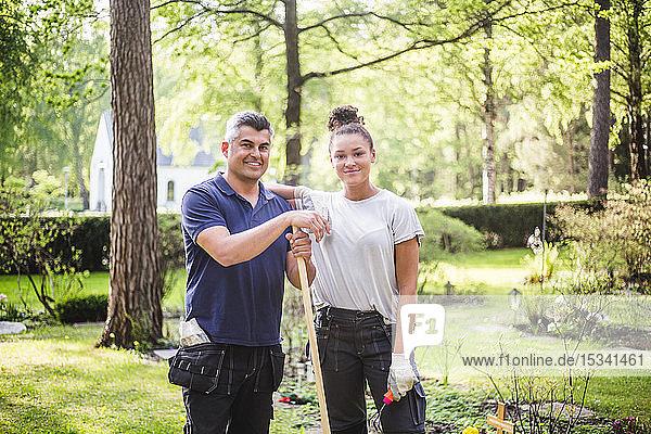 Porträt einer lächelnden Auszubildenden  die mit der Hand auf der Schulter des Lehrers im Garten steht
