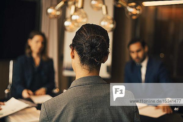 Rückansicht einer Rechtsanwältin mit Kollegen bei einem Treffen in einem Rechtsbüro