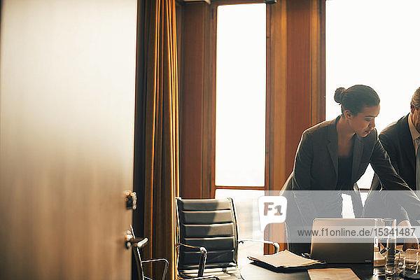 Männliche und weibliche Kollegen diskutieren am Konferenztisch in einer Anwaltskanzlei