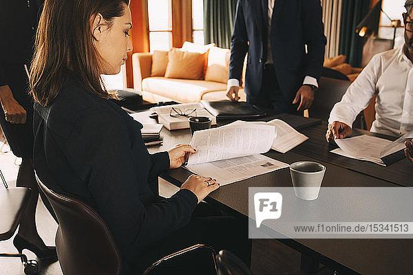 Weibliche Anwältin liest Dokument  während sie mit Kollegen im Sitzungssaal im Büro sitzt