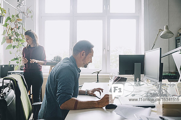 Side view businessman using laptop at desk in creative office