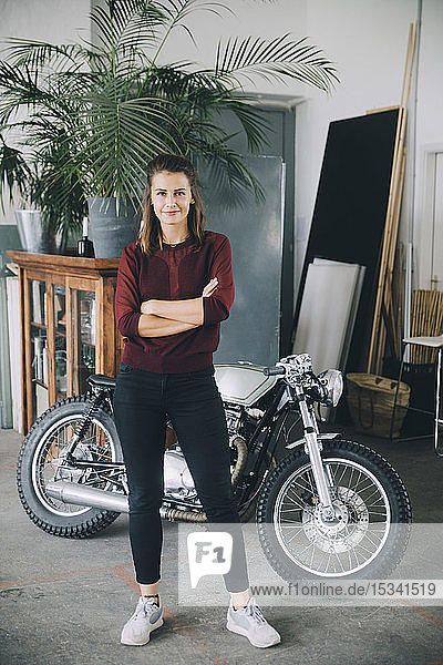 Portrait of confident female entrepreneur standing with arms crossed against motorcycle in creative office