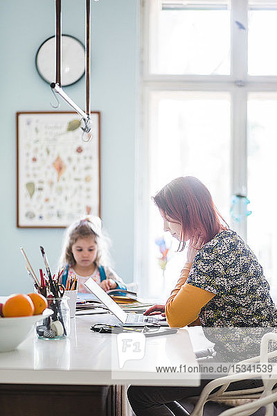 Side view of mid adult women working on laptop while sitting with girl at kitchen island