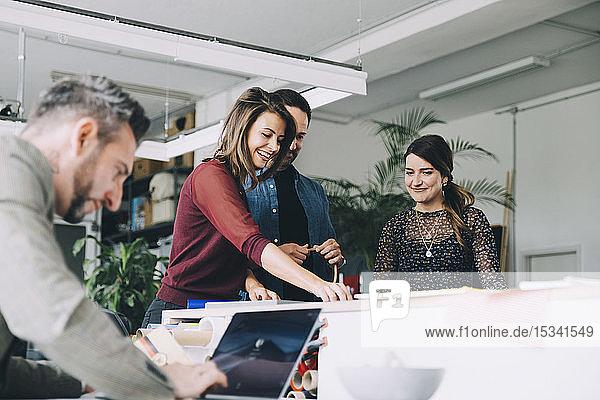 Lächelnde Geschäftsfrau arbeitet mit Kollegen zusammen  während ein Geschäftsmann seinen Laptop im Kreativbüro benutzt