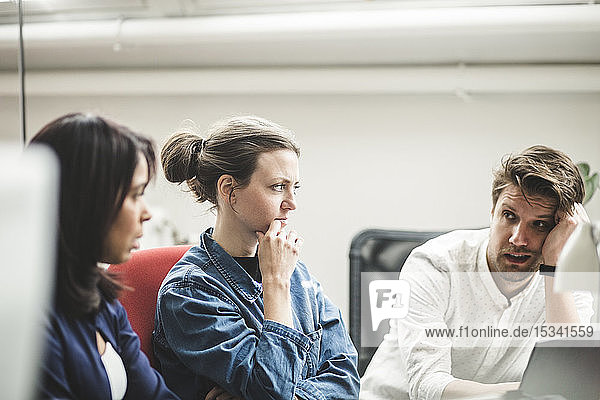 Geschäftsmann diskutiert mit weiblichen Fachleuten bei Treffen im Kreativbüro