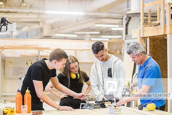 Männlicher Ausbilder erklärt Auszubildenden an der Werkbank den Bohrer auf einem Brett