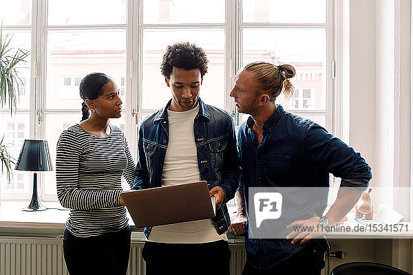 Male entrepreneur holding laptop while discussing with colleagues against window in office