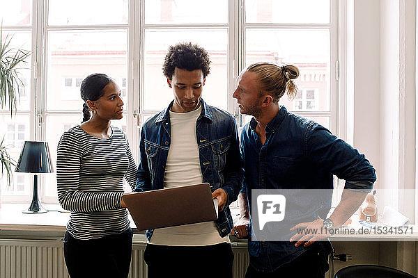 Männlicher Unternehmer hält Laptop in der Hand  während er mit Kollegen gegen Fenster im Büro diskutiert