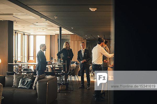 Lächelnde männliche und weibliche Fachleute in der Kaffeepause in einer Anwaltskanzlei