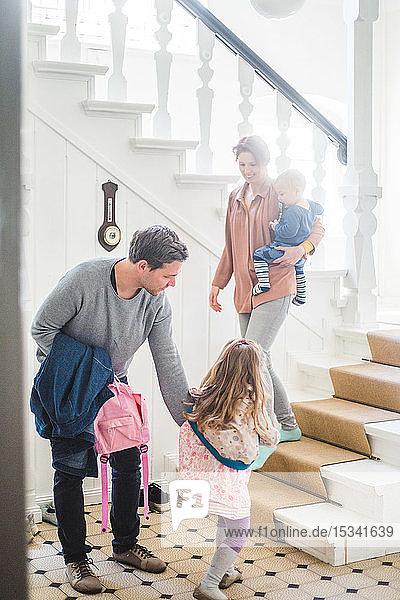 Mutter mit Sohn sieht Mann an  der seine Tochter auf die Schule vorbereitet