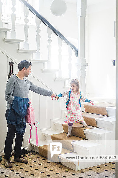 Full length of father holding schoolgirl moving down steps at home