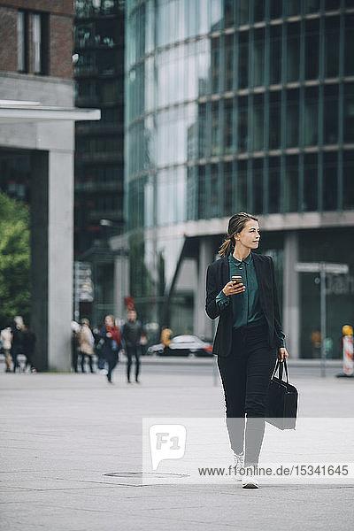 Selbstbewusste Geschäftsfrau in voller Länge  die beim Gehen auf der Straße in der Stadt wegschaut