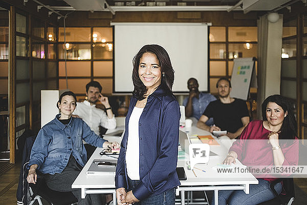 Portrait of confident female manager standing with team in background at office